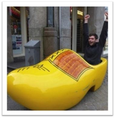 Studen sitting in a large wooden shoe